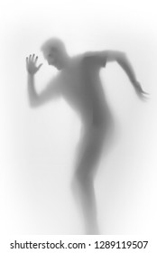 Happy dancing man body silhouette behind a diffuse surface. Face, head, fingers and hand can be seen.