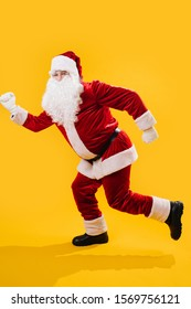 Happy dancing Santa Claus doing a version of a modern walking man dance, stepping on one foot at a time. Over yellow background. Looking at camera.