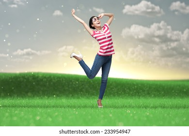 Happy dancing teenager with arms up in the park
