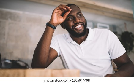 Happy dark skinned bearded male writer looking away enjoying creative process of making articles, smiling african american handsome hipster guy satisfied with education doing homework dreaming