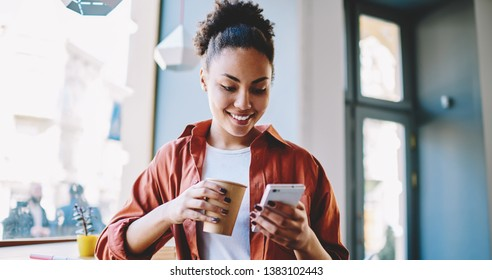 Happy dark skinned hipster girl sending sms message via smartphone device while enjoying caffeine beverage, african woman holding paper cup with coffee and reading article on content funny website