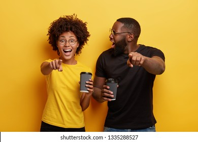 Happy dark skinned woman and her boyfriend being emotional, surprised, point at camera, laugh at something funny, drink takeaway coffee, enjoy free time together, react on something astonishing