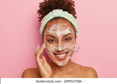 Happy dark skinned woman pampers face with bubble cleansing foam, has hygienic treatments in bathroom, massage cheeks, wears headband and round earrings, enjoys softness of skin, smiles positively