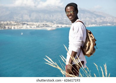 Happy dark-skinned backpacker in white sweater and black hat standing on the edge of cliff above seaside, looking glad and grateful for admiring such amazing view. People, lifestyle and traveling