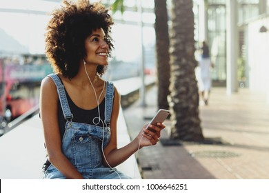 a happy dark-skinned girl enjoys music from her playlist through headphones. girl uses a mobile phone to watch a new video of her favorite artist. Female person listening online radio via cellphone
