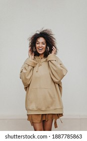 Happy dark-skinned girl smiles widely and listens to music in headphones on grey background. Curly woman in hoodie poses.