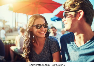 happy dating couple at outdoor restaurant with lens flare and shot with selective focus