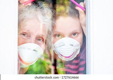 Happy daughter and elderly mother in a respiratory masks having fun near the window of house. Family fun. Stay at home. Drawing a smile on protective masks. Quarantin, isolated. Coronavirus covid-19.