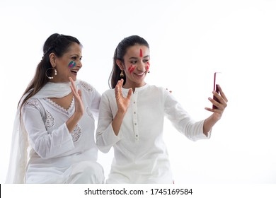 Happy daughter holding phone taking selfie on cellphone with mother isolated on white background.