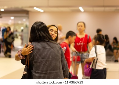 Happy daughter hugging mother on arrival at the airport