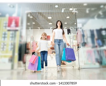 Happy daughter keeping hand of attractive mother and going out from store in mall. Cheerful Family shopping and buying new clothes in boutiques, looking at camera and laughing. Concept of retail.