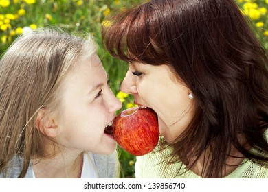 Happy daughter and mother  biting apple together