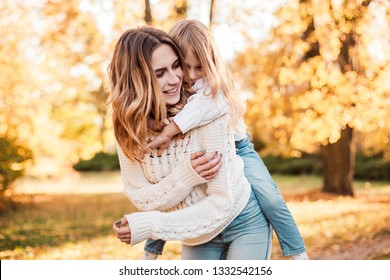 Happy daughter with mother is having fun walking in the park.
