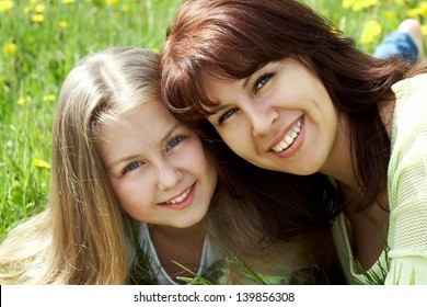 Happy daughter and mother lying on meadow
