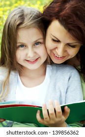 Happy daughter and mother reading book �¢?? education outdoor