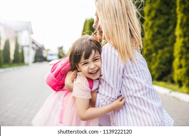 Happy daughter and pretty mother embracing each other on sidewalk next to the trees. Mom play together with kid preschooler with backpack outdoor. Mom and child have fun. Mother's day concept.