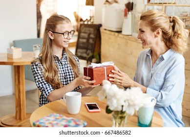 Happy daughter receiving a present from her mother
