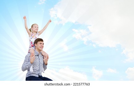 Happy daughter sitting on shoulders of her father