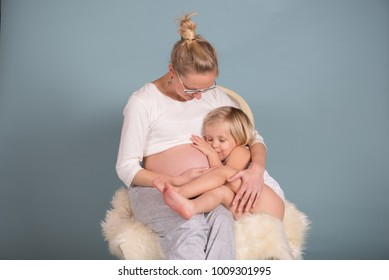 Happy daughter snuggle up to her pregnant mother