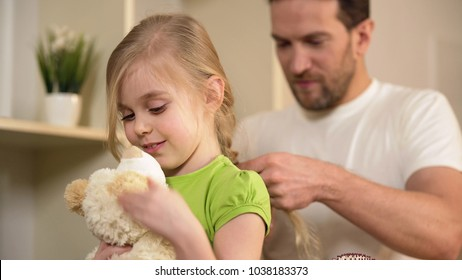 Happy daughter waiting father braiding her blonde hair, playing with teddy-bear