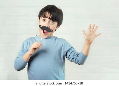 Happy father´s day,boy with false mustache on stick on brick background