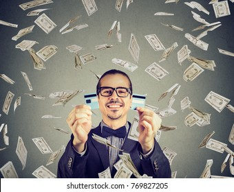 Happy debt free man holding a credit card cut in two pieces under money rain