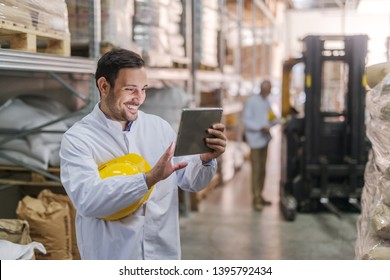 Happy dedicated young Caucasian worker with helmet under the armpit using tablet while standing in warehouse. In background worker and forklift.