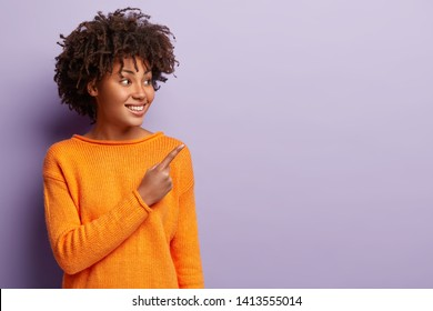Happy delighted Afro American woman shows friend new product, persuades to buy this object, feels amused and satisfied, wears orange jumper, isolated over purple background. Look at awesome promo