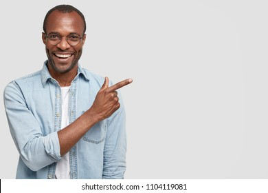 Happy delighted male manager involved in advertising company`s product, indicates with fore finger at blank copy space, wears denim shirt, has positive smile. Advertisement and ethnicity concept