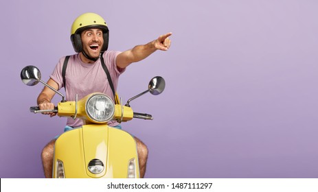 Happy delighted man points into distance, notices something cool and awesome, wears protective helmet, drives motorbike, has long trip or journey, isolated on purple background. Driver on moped