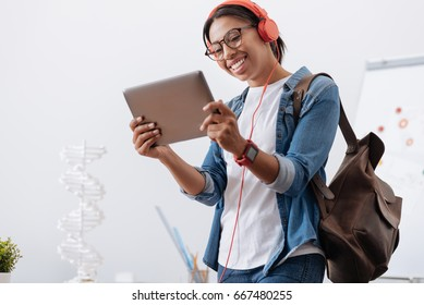Happy delighted student holding a tablet