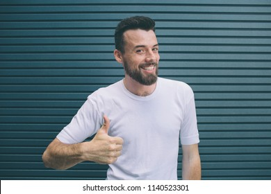 Happy and delightful man is showing his big thumb up. Also guy is looking at camera and smiling. He is posing. Isolated on striped and blue background.