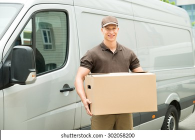 Happy Delivery Man Holding Box In Front Van