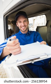 Happy delivery man showing clipboard to sign to customer outside the warehouse