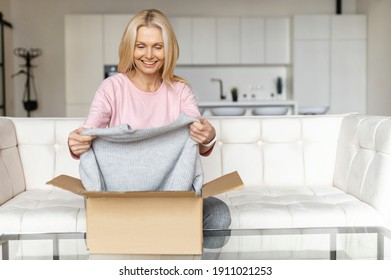 Happy with delivery satisfied female customer unpacking cardboard box, excited middle-aged woman glad to get a parcel, order online, sitting on the couch at home