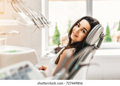 Happy dental patient in the dental chair