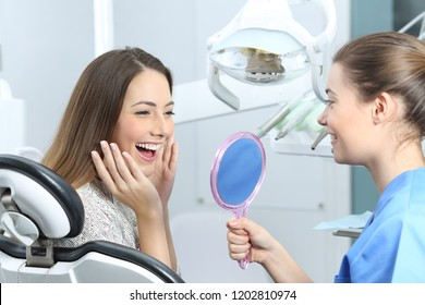 Happy dentist patient checking whitening results looking in a mirror