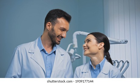 happy dentists in white coats looking at each other in clinic