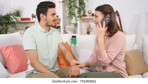 Happy Dialogue of Young Couple Talking on Mobile Phone with Family in Home Sofa