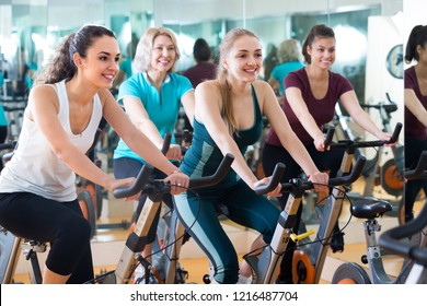 Happy different age women cycling on exercise bikes at fitness club . Selective focus