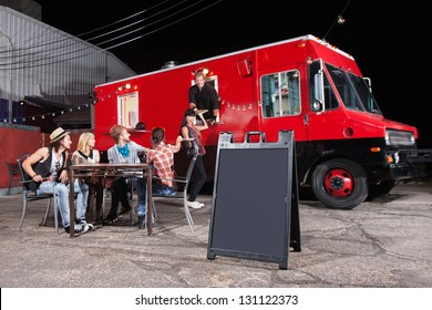 Happy diners at food truck with blank sign