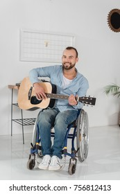 happy disabled man on wheelchair playing guitar