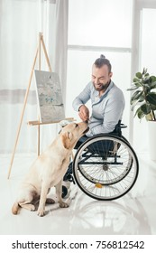happy disabled man on wheelchair painting and playing with dog