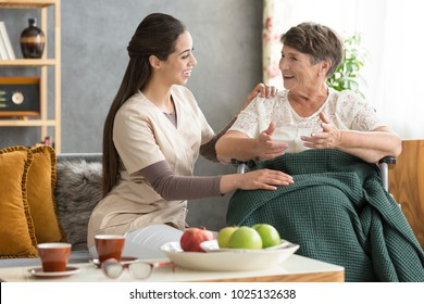Happy, disabled, senior woman talking to a friendly caregiver