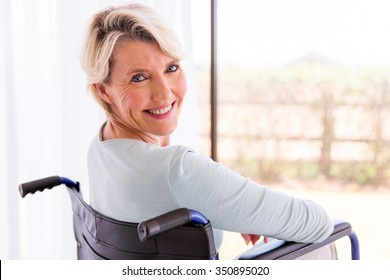 happy disabled woman in wheelchair looking back