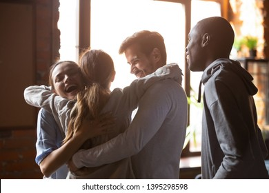 Happy diverse best friends embracing, greeting in cafe at sudden meeting, standing together, excited multiracial students or colleagues group in good friendly relations, reunion concept
