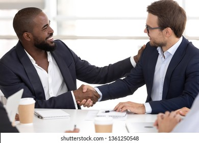 Happy diverse business men reliable male partners shake hands at meeting negotiation concept, promotion reward handshake express respect trust gratitude, successful teamwork partnership collaboration
