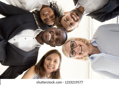 Happy diverse business people team gathering in circle looking at camera, smiling multiracial employees group bonding together, corporate unity and teambuilding concept, view from below, portrait