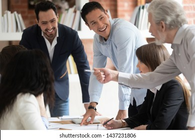 Happy diverse business team young and old employees talking brainstorming on project paperwork gather at conference table, smiling workers group engaged in teamwork at corporate briefing in boardroom