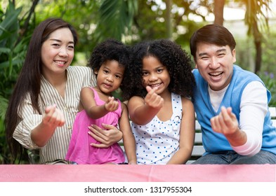 Happy Diverse children enjoying playing with Family. Kids care,family, charity. Hand making mini heart with baby and adult Voluntary non profit organization or Exchange Student or healthcare concept.